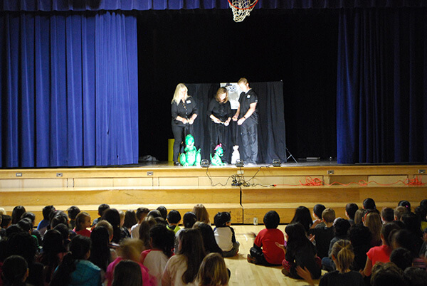 puppeteers perform puppet show in front of large group of elementary school students