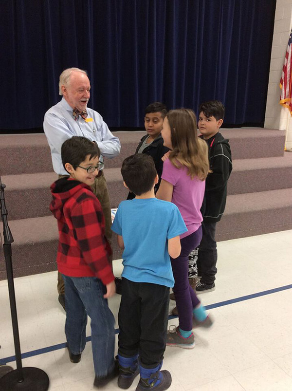 students visit with storyteller after performance