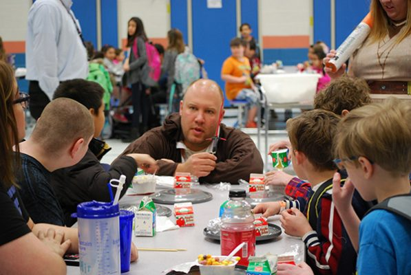 principal dressed as jedi talks to students eating breakfast