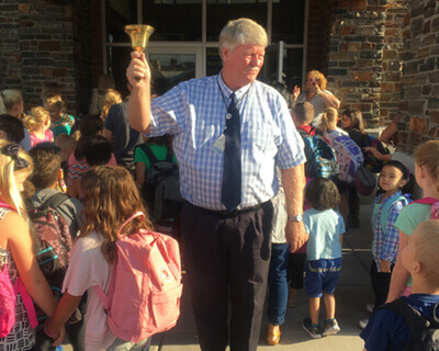 Dean Nielsen with school bell