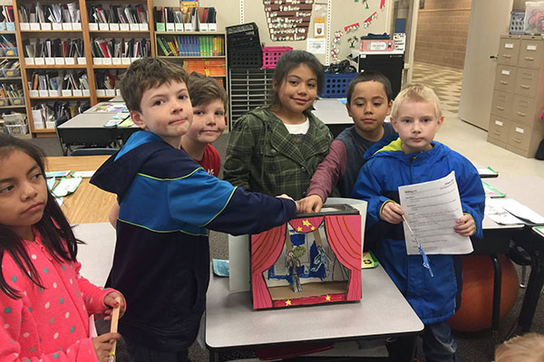 a group of students pose by their puppet show