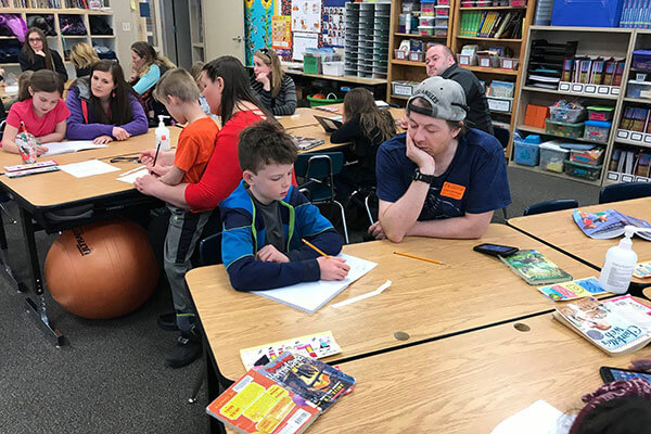 son and dad work together in classroom
