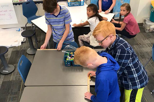 students work together to measure desk