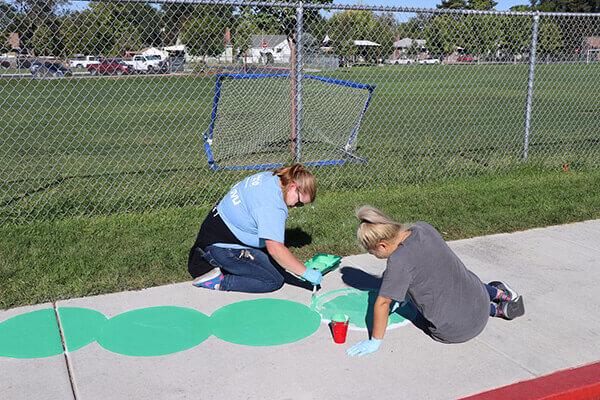 volunteers painting the sidewalk