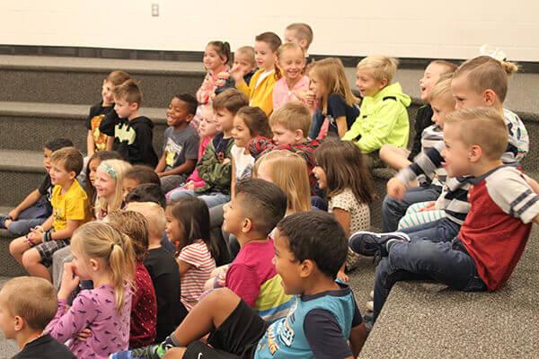 students listen to teacher reading a book