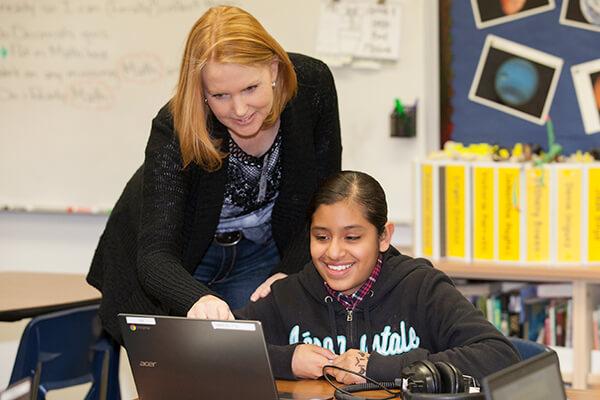 teacher with student on Chromebook
